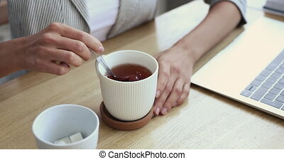 Woman adding sugar cube into cup of tea, closeup view - ...