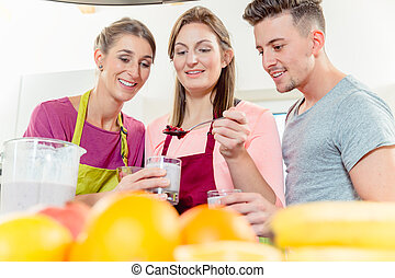 Woman adding toppings over the smoothie in the glass