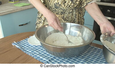 Woman adds flour to the water and makes dough in the kitchen