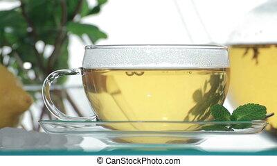 Woman adds sugar in glass of tea