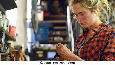 Woman adjusting a tool at workshop 4k - Beautiful woman...