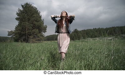 Woman adjusting hair on field - Young woman taking a walk in...
