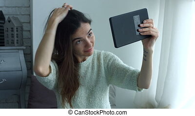 Woman adjusting her hair using tablet as mirror