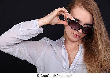 Woman adjusting her sunglasses