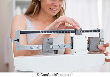 Woman adjusting scale - Woman adjusting medical scale