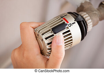 Woman Adjusting The Thermostat - Woman Hand Adjusting The...