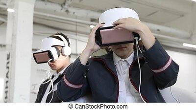 Woman adjusts VR-headset man puts off headphones