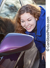 Woman admire oneself in car rear-view side mirror