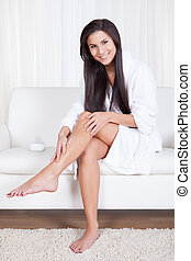 Woman admiring her bare legs - Beautiful young woman sitting...