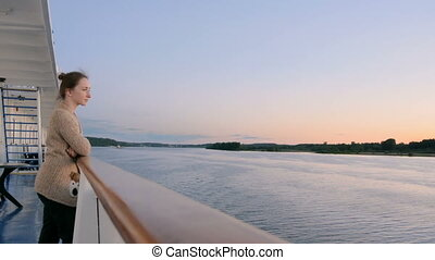 Woman admiring landscape from deck of cruise ship after sunset