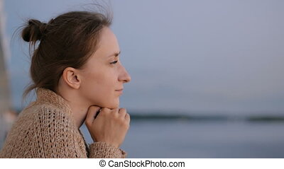 Woman admiring landscape from deck of cruise ship after...