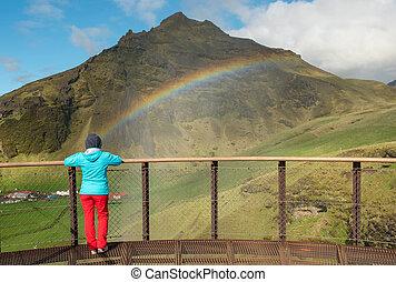 Woman admiring rainbow over the Skogafoss waterfall in Iceland