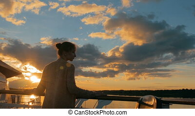 Woman admiring sunset from deck of cruise ship - Woman...