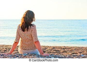 woman admiring the sea while sitting on a pebble beach