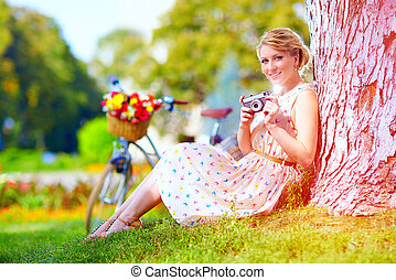 woman after bicycle ride relaxing with camera