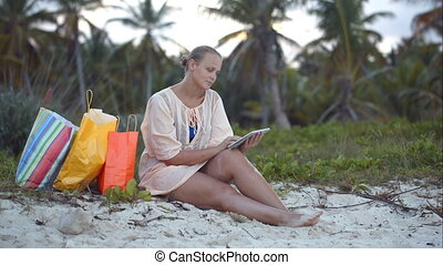 Woman after shopping using tablet PC on the beach