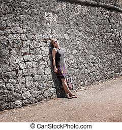 woman against old stone wall