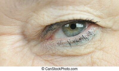 Woman aged 60s opens and closes up one eye. Close up