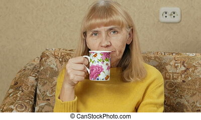 Woman aged drinking a hot drink from a cup at home on the couch and looking at the camera. She is resting after a hard day. holiday concept