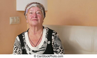 Woman aged seriously looking at the camera and looks around. Portrait of a pensive woman at home on the couch