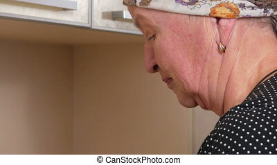 Woman aged washes dishes at home in the kitchen. Close-up face