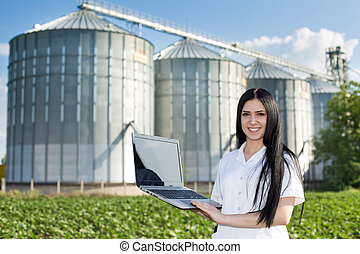 Woman agronomist in front of silo - Young woman agronomist...