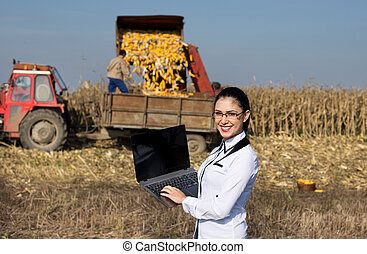 Woman agronomist with laptop in corn field