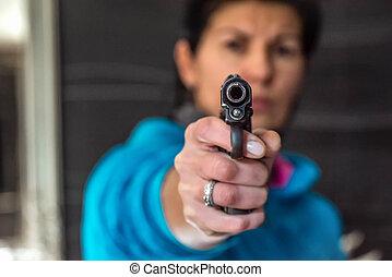 Woman aiming gun at the camera