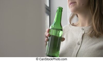 woman alcoholic drinking beer from bottle at home