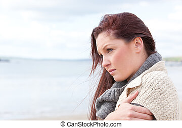 Woman all alone on the beach looking the side