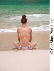 woman alone sit on the beach looking sea and island