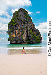 woman alone sit on the beach looking sea and island.