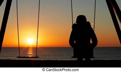 Back view silhouette of a sad woman alone swinging looking at empty seat at sunrise