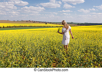Woman among a field of canola plants flowering in spring sun