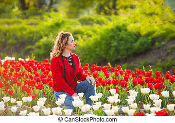 Woman among a field of red and white tulips