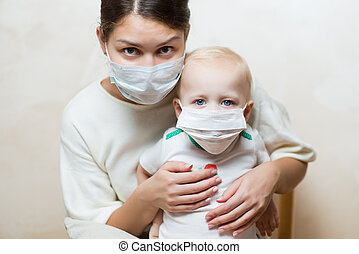 woman and a baby in medical masks, close up