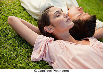Woman and a man with their eyes closed lying head to shoulder with their arms resting behind their neck on the grass
