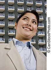 beautiful young woman standing in front of a hotel or apartments.