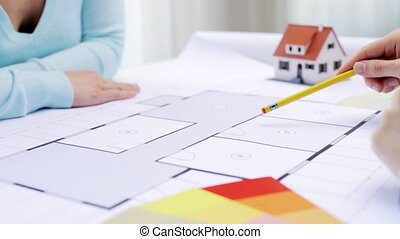 architecture, building, construction, real estate and people concept - woman and male architect discussing blueprint of living house at home or office