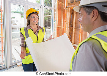 Woman and architect discussing blueprint in house site