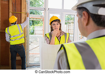 Woman and architect talking while man is measuring wooden frame