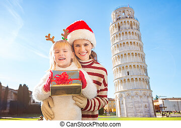 Woman and baby girl with gift box spending Christmas in Pisa