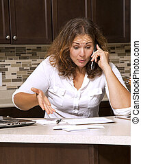 woman and bills - stressed woman looking at bills while...