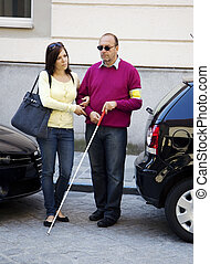 Woman and blind, visually impaired man - A young woman helps...