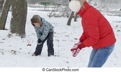 Woman and boy playing snowballs in the snow