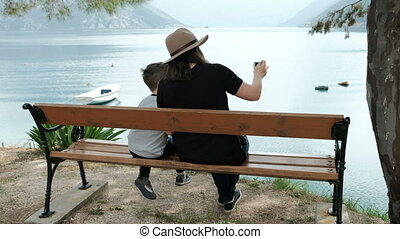 Woman and boy sitting facing sea taking pictures on phone.