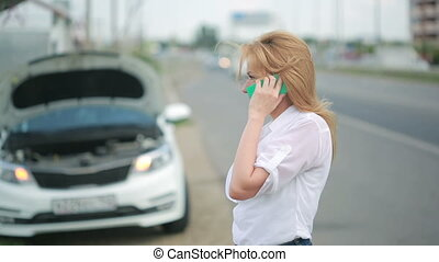 woman and broken car calling for help on cell phone. broken car on the road