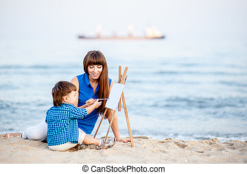 Woman and child draw on the easel