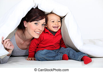 Woman and child hiding under a duvet