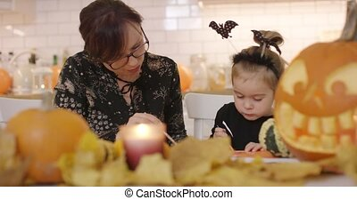 Woman and child making decorations - Woman in glasses and...